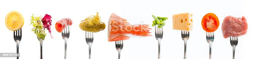 Products on fork on white background.