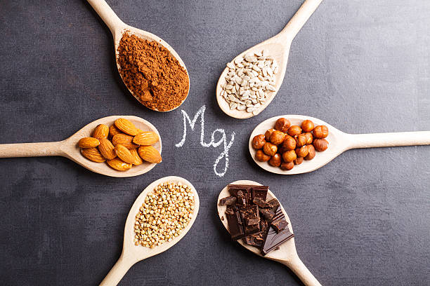 products rich in magnesium on wooden spoons. - magnesium stock photos and pictures