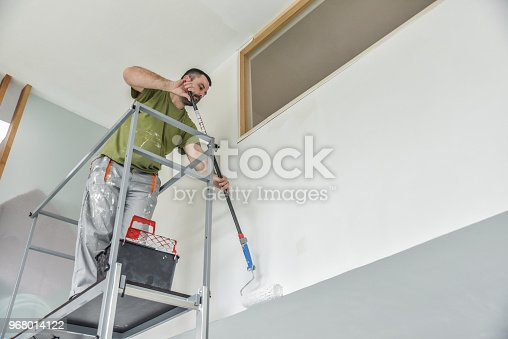Profesional painter painting with paint roller. Decorator at work painting a wall.