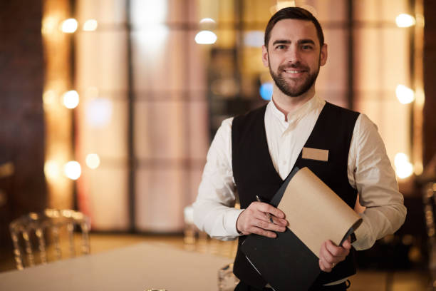 Profesional Waiter in Restaurant Waist up portrait of handsome waiter smiling cheerfully at camera standing in luxury restaurant or cafe, copy space waiter stock pictures, royalty-free photos & images