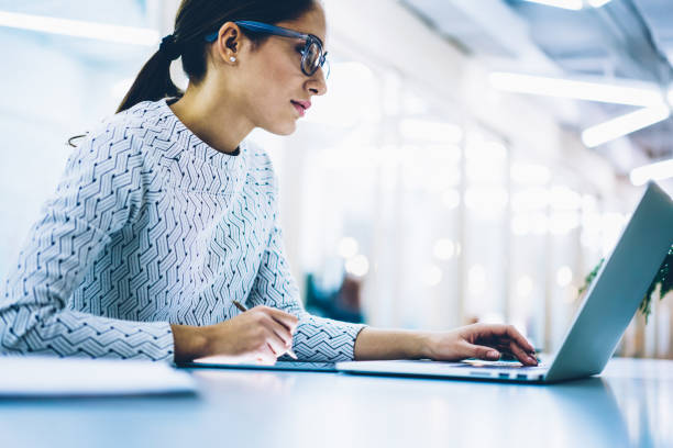 Professional administrative manage in spectacles for eyes protection checking content of company website on laptop computer, serious female secretary making booking on netbook working in office stock photo