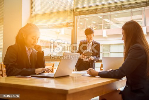 istock Professional administrative short black hair asian business woman hold book in hand and work with ladies co-worker in workplace,communication technology banking concept. 694532976