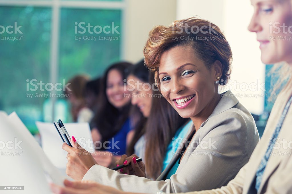 Professional African American businesswoman is smiling during business conference stock photo