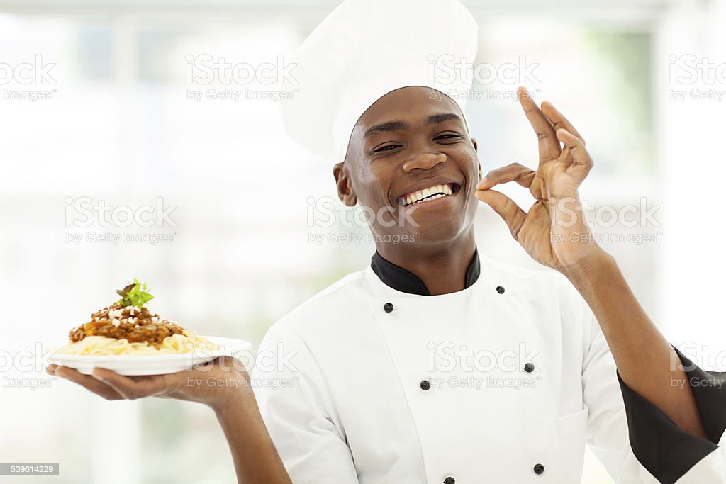 professional African chef holding delicious spaghetti stock photo