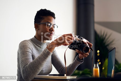 istock Professional afro american woman photographer in trendy eyewear checking settings on camera taking pictures, talented designer viewing images on equipment earning money editing photo and video files 907952172