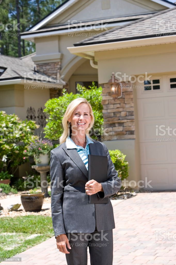 Professional agent in business suit standing outside house stock photo