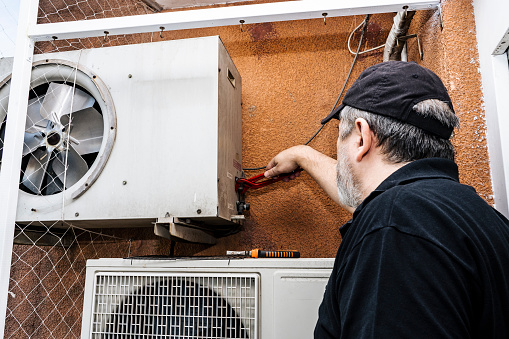 Professional air conditioning technician adjusting the refrigerant outlets on an external unit of a old split air unit.