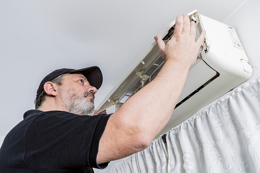 Professional air conditioning technician checking the cover of an internal unit of a split air unit. Professional job concept