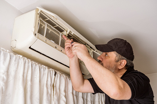 Professional air conditioning technician checking the filters of an indoor unit of a split air system.
