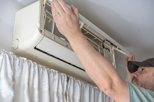 Professional air conditioning technician lifting the cover of an indoor unit of a split air system to check the operation.