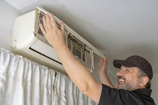 Professional air conditioning technician lifting the cover of an indoor unit of a split air system to clean and fix the unit.