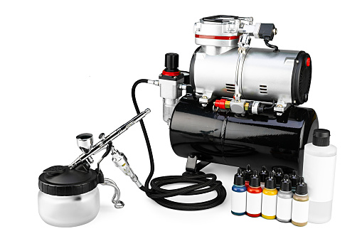 professional airbrush compressor starter set equipment with chrome metal gun acrylic paint and thinner bottles isolated on white background. Industry hobby and art concept.