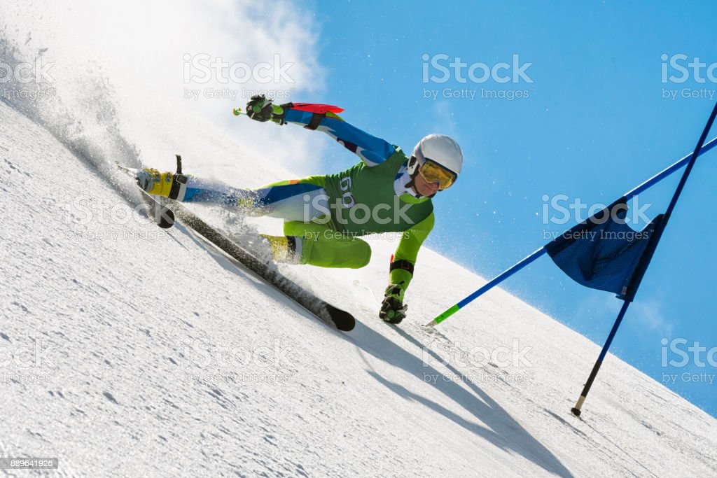 Professional Alpine Skier Compeeting at Giant Slalom Race Against the Blue Sky stock photo