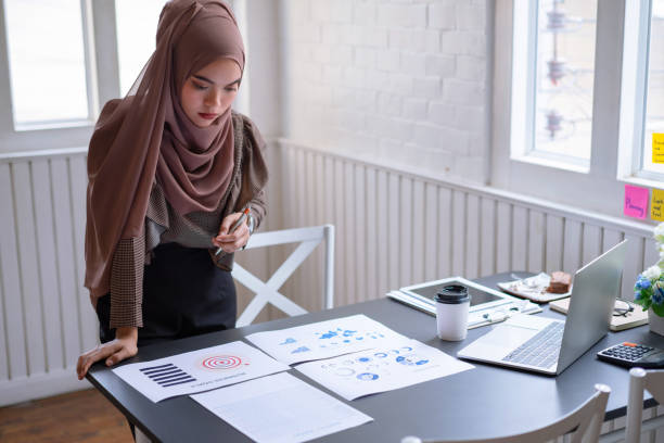 Professional arab businesswoman brown hijab standing and checking in financial investment project graph chart report. indoor Professional arab businesswoman brown hijab standing and checking in financial investment project graph chart report. indoor business Malaysia stock pictures, royalty-free photos & images
