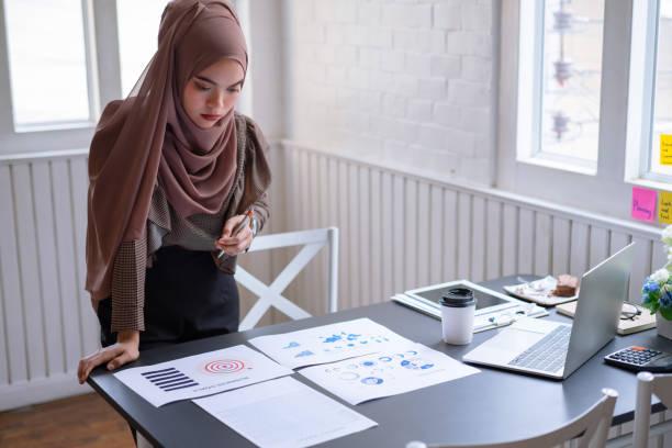 femme d'affaires arabe professionnelle brun hijab restant et vérifiant dans le rapport graphique de graphique de projet d'investissement financier. d'intérieur - business malaysia photos et images de collection