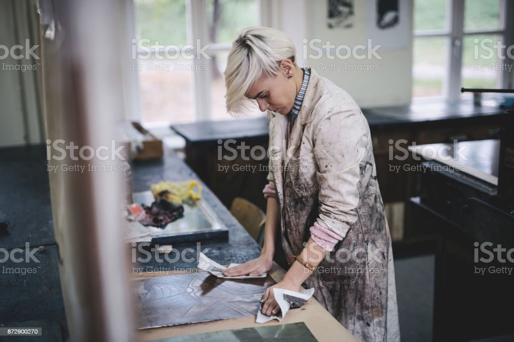 Professional artist working on new etching metal plate stock photo