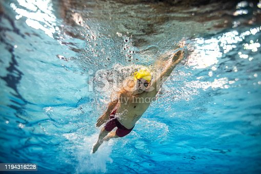Underwater shot of young man practicing front crawl style of swimming in the swimming pool.
