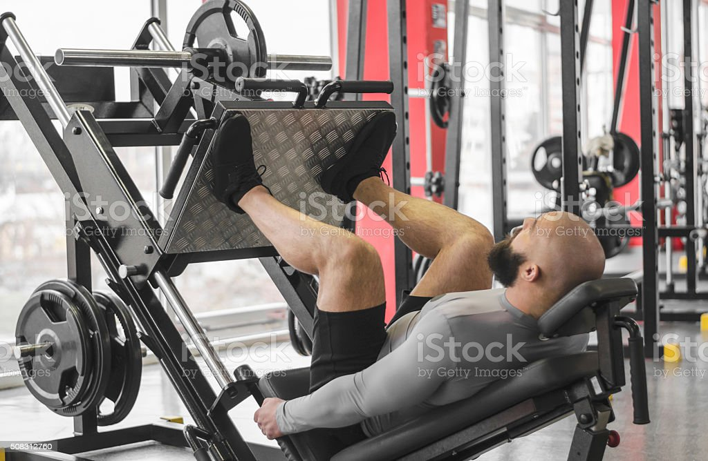 Professional athlete doing leg day routine at gym, preparing stock photo