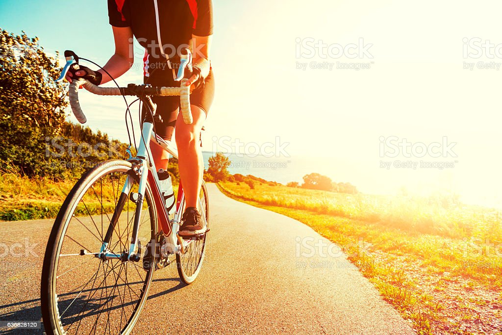 Professional athlete rides bicycle up a hill at sunset - foto de acervo