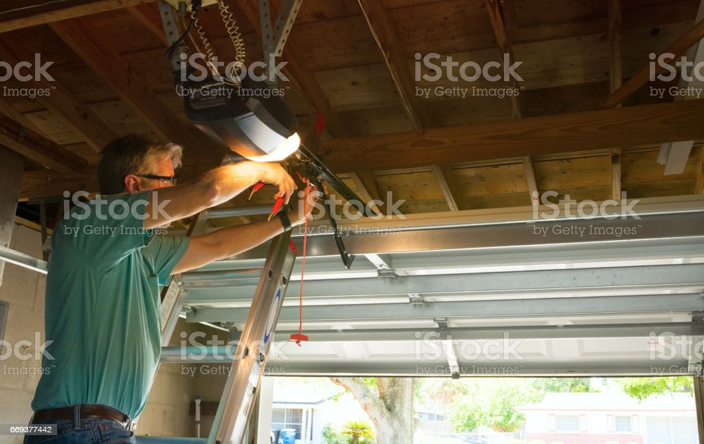 Professional automatic garage door opener repair service technician man working stock photo