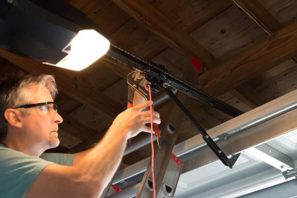 Professional automatic garage door opener repair service technician working closeup stock photo