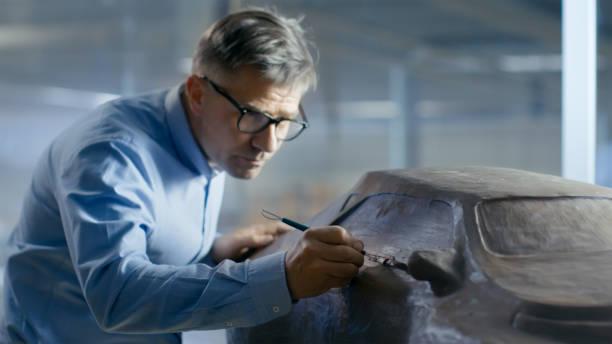 professionelle automobil-designer mit rechen formt futuristisches automodell aus plastilin ton. er arbeitet in einem speziellen studio befindet sich in einem großen automobilwerk. - skulpturprojekte stock-fotos und bilder