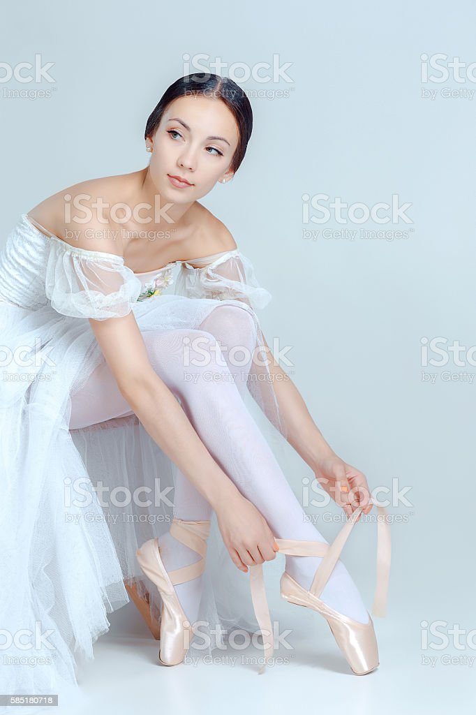 Professional ballerina putting on her ballet shoes stock photo