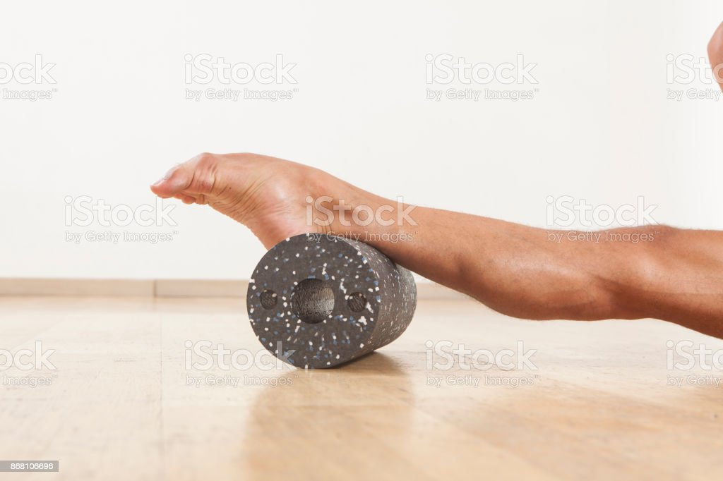 professional ballet dancer stretching and warming up using foam roller stock photo
