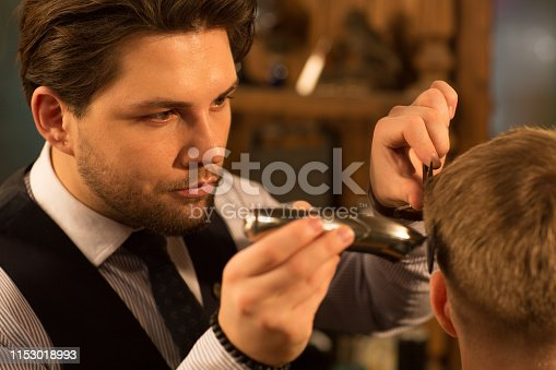 Close up of a handsome professional barber looking focused and concentrated giving a haircut to his client profession occupation job work fashion hairdresser hairstylist hair care tools trimmer clipper.