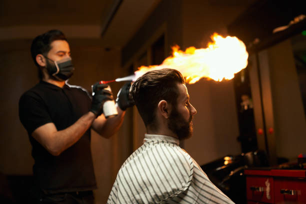 Professional barber doing haircut with fire treatment stock photo