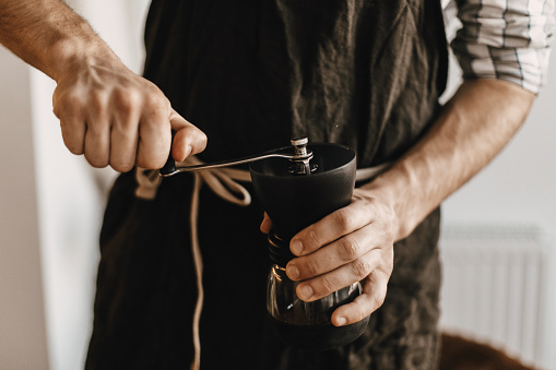 Professional barista in black stylish apron grinding coffee for aeropress, alternative brewing method. Hands holding manual grinder  with coffee beans. Items for an alternative coffee