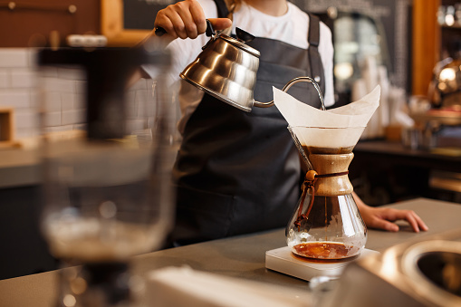 Professional barista preparing coffee using chemex pour over coffee maker and drip kettle.