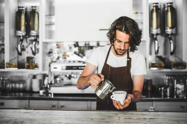 a professional barista working in a cafe, preparing coffee. copy space. - barista stock photos and pictures