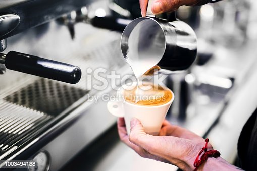 An unrecognizable man standing in a coffee shop, pouring milk in a cup of coffee.