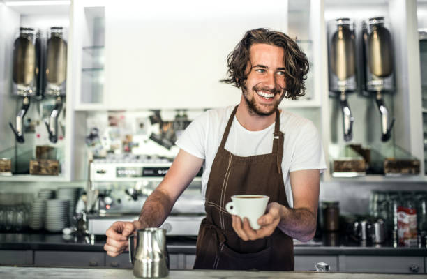 A professional barista working in a cafe, preparing coffee. A handsome man standing in a coffee shop, holding a jar with milk and a cup of coffee. barista stock pictures, royalty-free photos & images