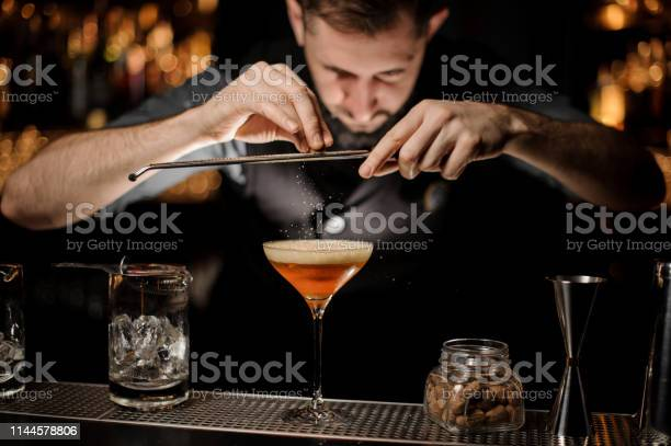 Professional bartender adding to a cocktail in the glass with a a picture id1144578806?b=1&k=6&m=1144578806&s=612x612&h=hmywyjzv8r8naljuuei332y durrag1y6ulelomuqwi=