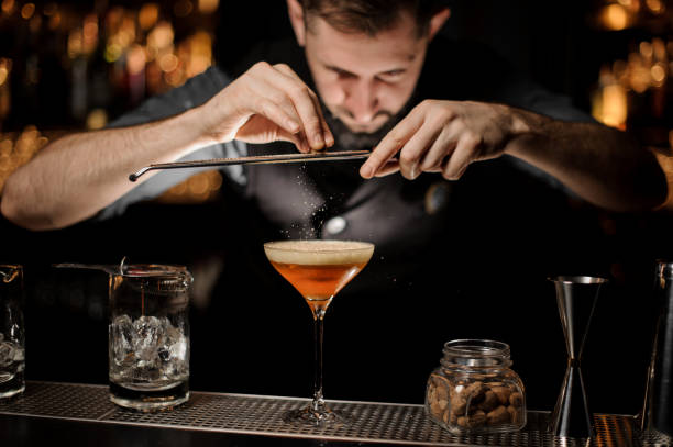 Professional bartender adding to a cocktail in the glass with a whipped cream a grated nutmeg Professional bartender adding to a cocktail in the glass with a whipped cream a grated nutmeg on the bar counter in the dark blurred background. bartender stock pictures, royalty-free photos & images