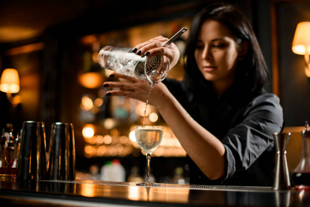 Professional bartender girl pouring a trasparent alcoholic drink from the measuring cup to the glass through the strainer filter Professional bartender girl pouring a trasparent alcoholic drink from the measuring cup to the glass through the strainer filter on the bar counter bartender stock pictures, royalty-free photos & images