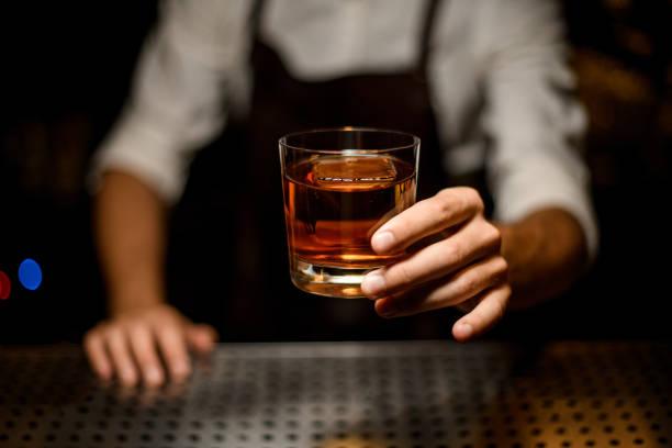 하나의 큰 아이스 큐브와 함께 유리에 칵테일을 제공하는 전문 바텐더 - bartender 뉴스 사진 이미지
