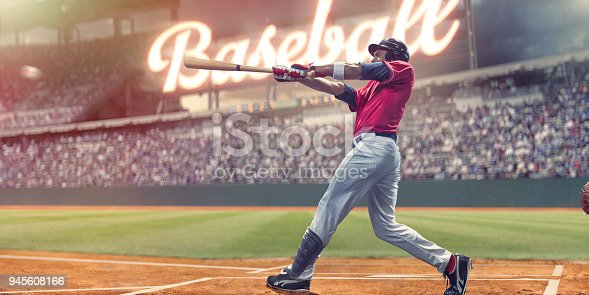 Professional baseball player with baseball bat outstretched having just struck baseball during an outdoor baseball game. The batter is dressed in generic white and red baseball uniform with black safety helmet and stands in the batters box in front of spectators and a bright neon sign in a generic stadium.