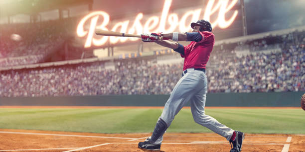 Professional Baseball Batter Striking Baseball During Night Game In Stadium stock photo