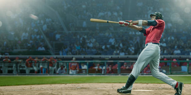 Professional Baseball Player Hits Ball In Mid Swing During Game stock photo