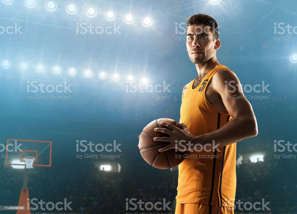 Young professional basketball player holding a ball. Medium close-up