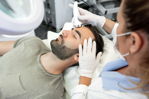 Professional Beautican Provides Ultrasound Facial Treatment Professional Beautican Provides Ultrasound Facial Treatment tighten stock pictures, royalty-free photos & images
