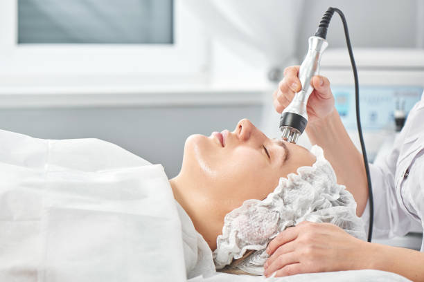 Professional beautician in office conducts session of thermal or radio frequency hardware RF lifting. Tightening and rejuvenation of face skin woman patient close up