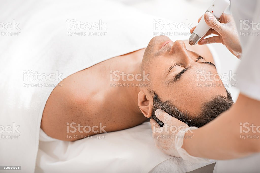 Professional beautician rejuvenating male face stock photo