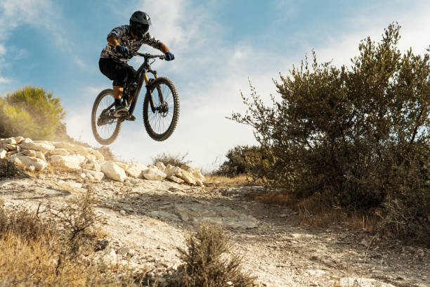 Professional bike rider jumping during downhill ride on his bicycle stock photo