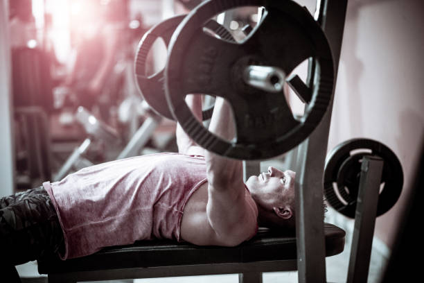 Professional body builder lifting weights on bench press stock photo