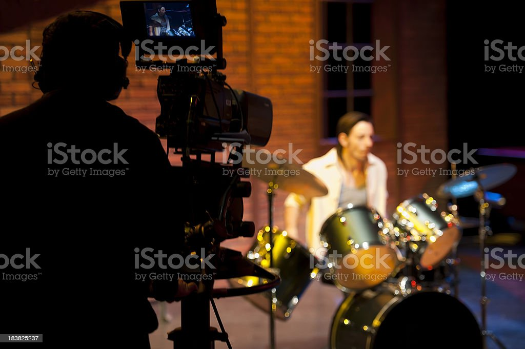 Professional broadcast video camera in studio shooting musician stock photo