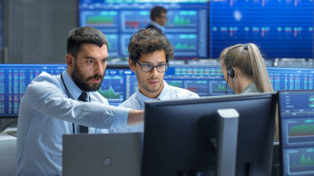 Professional Broker Consults Stock Exchange Trader at His Workstation. Multi-Ethnic Team at Stock Exchange Office is Busy Selling and Buying Stocks on the Market. Displays Show Relevant Data Numbers. stock photo